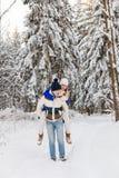Il tipo e la ragazza hanno un resto nel legno dell'inverno immagini stock libere da diritti