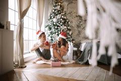 Il tipo e la ragazza in magliette e cappelli bianchi di Santa Claus si siedono con le tazze rosse sul pavimento davanti alla fine fotografie stock