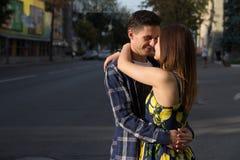 Il tipo e la ragazza stanno baciando sui precedenti della strada, la città immagini stock