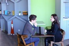 Il tipo e le studentesse si rilassano in biblioteca dopo la scuola e si siedono alla t Fotografia Stock