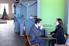 Il tipo e le studentesse si rilassano in biblioteca dopo la scuola e si siedono alla t Fotografie Stock Libere da Diritti