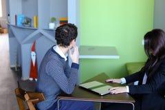 Il tipo e le studentesse si rilassano in biblioteca dopo la scuola e si siedono alla t Immagini Stock