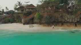 Il tipo e una ragazza stanno correndo alla costa con le case Tempo di sera La bella natura delle Filippine Siluetta dell'uomo Cow stock footage
