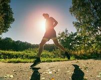 Il tipo esile del corpo funziona sul percorso con le foglie cadute Giorno caldo fotografie stock