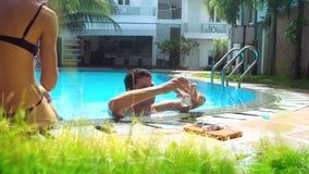 Il tipo fa il selfie in stagno che la ragazza esile in bikini si siede sulla barriera video d archivio