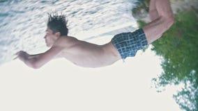 Il tipo fa un'immersione subacquea nell'acqua dalla roccia, la vista dal basso, movimento lento di vibrazione archivi video