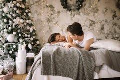 Il tipo felice e la ragazza vestiti in magliette bianche stanno trovando su un letto e stanno esaminandose immagine stock