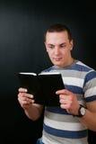 Il tipo fissa in un libro Immagini Stock