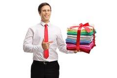Il tipo formalmente vestito che tiene una pila di rivestito di ferro di e di imballato di copre fotografia stock