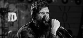Il tipo gradisce cantare nel modo aggressivo Musicista con la canzone di canto dei baffi e della barba nel karaoke Concetto del r fotografia stock libera da diritti