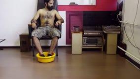 il tipo Indù di aspetto con il torso nudo si siede sulla sedia, mette i piedi nel washbawl del yelllow video d archivio