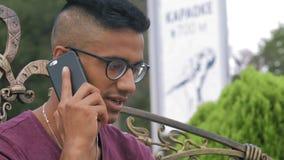 Il tipo indiano del primo piano in occhiali parla sul telefono che si siede su un banco nel parco stock footage