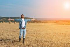Il tipo in jeans, camicia, stivali di gomma nel campo con le sue mani si apre, il concetto di libertà, la motivazione, il movimen fotografia stock