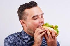 Il tipo mangia un hot dog che egli stesso ha preparato Alimento della via immagine stock libera da diritti