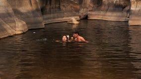 il tipo mostra alla ragazza alla nuotata in lago creato tramite la torrente montano stock footage