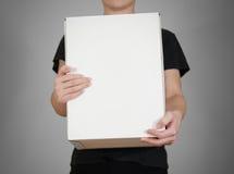 Il tipo nella camicia nera che tiene una grande scatola bianca Porta la a Immagine Stock