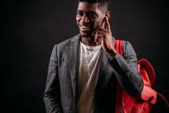 Il tipo nero sorridente dei giovani sta parlando con la sua amica con le cuffie Fotografia Stock Libera da Diritti