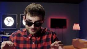 Il tipo osservato grigio sveglio ha messo sopra gli occhiali da sole parla, balli e strizzatine d'occhio alla macchina fotografic video d archivio