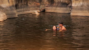 il tipo porta dentro arma la nuotata d'aiuto della ragazza in lago creato tramite la corrente stock footage