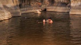 il tipo porta dentro arma la nuotata d'aiuto della ragazza in lago creato tramite la corrente archivi video