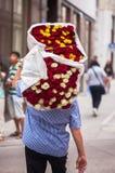 Il tipo porta un grande mazzo con le rose rosse, bianche e gialle fotografia stock