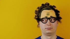 Il tipo riccio divertente gira o rotola i suoi occhi, emozioni allegramente umane pazze, sul fondo giallo della parete, capelli n archivi video