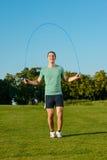 Il tipo salta su un salto della corda su un prato verde Immagini Stock