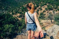 Il tipo segue la ragazza che tiene la sua mano che fa un'escursione il viaggio Immagine Stock Libera da Diritti