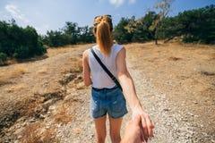 Il tipo segue la ragazza che tiene il suo viaggio dell'estate della mano Fotografia Stock