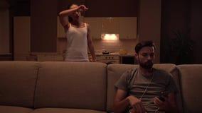 Il tipo si siede sul sofà e tiene il bpwl dei chip È mangiante ed ascoltante la musica La ragazza sta pulendo il pavimento dietro archivi video