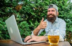 Il tipo si siede il terrazzo all'aperto con la birra Scommessa e gioco reale dei soldi Svago brutale dell'uomo con birra ed il gi fotografia stock