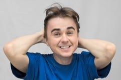 Il tipo sorridente tiene la sua testa Fotografie Stock Libere da Diritti