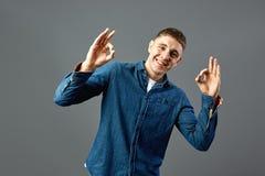 Il tipo sorridente vestito nelle manifestazioni di una camicia dei jeans con le sue dita approva i segni nello studio sui precede fotografia stock