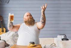 Il tipo spesso felice è riconoscente per la birra Fotografia Stock Libera da Diritti