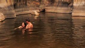 il tipo spiega alla ragazza alla nuotata in lago creato tramite la torrente montano video d archivio