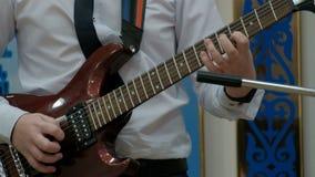 Il tipo spinge le corde con una scelta ed i cerchi dei morsetti delle dita su una chitarra sola Un adolescente in una camicia bia stock footage
