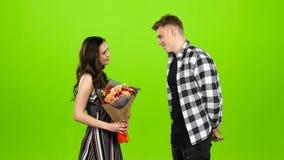 Il tipo sta aspettando la sua amica con un mazzo dei fiori, lei viene lui dà i fiori Schermo verde archivi video