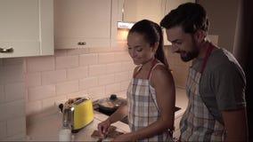 Il tipo sta dietro la ragazza e si tiene per mano sul suo Sta lubrificando il nutella su pane tostato che si tiene per mano sulle stock footage