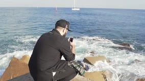 Il tipo sta fotografando le forti onde al pilastro stock footage
