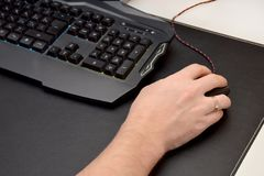 Il tipo sta giocando un video gioco Chiuda su di una mano che si trova su un topo e su una tastiera nera di gioco su una tavola n immagini stock