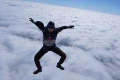 Il tipo sta sedendosi sopra le nuvole bianche immagine stock