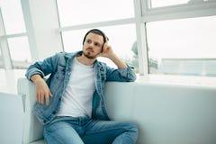 Il tipo sta sedendosi sul sofà e sul pensiero Immagini Stock