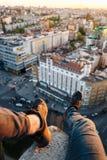 Il tipo sta sedendosi sull'orlo di un edificio alto Ha appeso le sue gambe con le belle scarpe da tennis nere sopra la città immagini stock