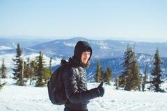 Il tipo sta stando nelle montagne nell'inverno Fotografia Stock