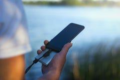 Il tipo sta tenendo un caricatore portatile con uno smartphone in sua mano Uomo su un fondo della natura con una pianta e un lago Fotografia Stock