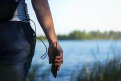 Il tipo sta tenendo un caricatore portatile con uno smartphone in sua mano Uomo su un fondo della natura con una pianta e un lago Immagine Stock