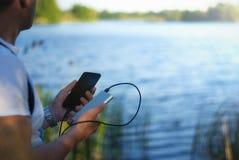 Il tipo sta tenendo un caricatore portatile con uno smartphone in sua mano Uomo su un fondo della natura con una pianta e un lago Fotografie Stock Libere da Diritti