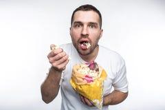 Il tipo stupito sta tenendo un piccolo pacchetto di buon popcorn e eting  Ha aperto la sua bocca Non sta mangiando il popcorn mol fotografie stock libere da diritti