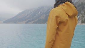 Il tipo sulla riva di un lago della montagna stock footage