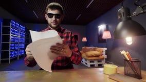 Il tipo sveglio intelligente con gli occhiali da sole mette il foglio di carta sullo scrittorio e lo legge sullo scrittorio archivi video
